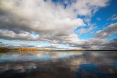 Mirror reflection of white clouds in a clear lake in the fall. Royalty Free Stock Photos