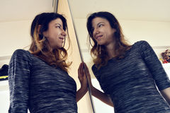 Mirror reflection. A woman playing with her reflection in the mirror Royalty Free Stock Photography