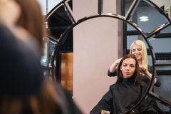Mirror reflection of young woman getting her hairdo by stylist Royalty Free Stock Photography