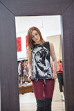 Mirror reflection of a young woman trying on clothes in fashion boutique Royalty Free Stock Photography