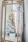 The mirror reflects the decorated Christmas tree, under the tree lie gifts.  royalty free stock photography