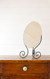 Mirror. Retro mirror on bedside table,  background white wooden wall Royalty Free Stock Images