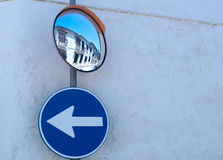 Mirror and road sign on the wall Stock Photos