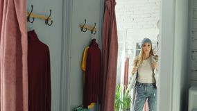 Mirror shot of young girl trying on clothes in fitting room. She is wearing denim jacket, jeans and hat, smoothing her. Hair, moving and looking in mirror to stock video