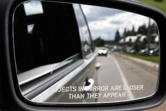 Objects in Mirror. A mirror on the side of a car states a warning: Objects in mirror may be closer than they appear stock photo