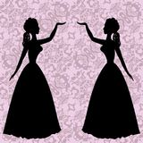 Mirror silhouettes dancing women on ornamental background in rococo style. Mirror silhouettes dancing women on ornamental pink background in rococo style Royalty Free Stock Images