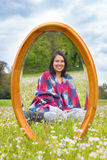 Mirror in spring meadow with sitting pretty woman. Mirror in blooming spring pasture with sitting pretty colombian woman Stock Image