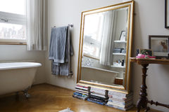 A mirror on stacks of books in a bathroom. Royalty Free Stock Images