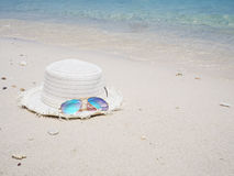 Mirror sunglasses and white hat on sand beach background Royalty Free Stock Images