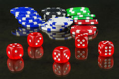 On mirror surface are casino chips and dices for playing poker Stock Photos