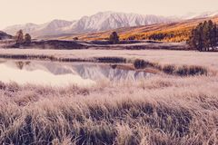 Mirror surface of the lake in the mountain valley. The peaks of the cliffs on the horizon at the colorful sky. royalty free stock photography