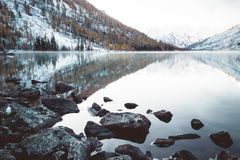 Mirror surface of the mountain lake. Beautiful nature. A trip to the mountains in a national Park in Altai Republic. Cloudy weather in winter royalty free stock photo