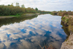 In the mirror surface waters of the river. Reflected clouds and blue sky Royalty Free Stock Photo