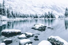 Mirror surface of the winter lake with a mountain range. First snow in the mountains. Travel to the national Park in the Altai mountains stock images