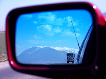 Mirror truck. A truck seen in a rear vierw mirror against winter landscape Stock Photos