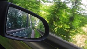 Mirror view from car driving in spring countryside. Mirror back view from car driving in spring countryside Landscape with trees and sunlight stock video footage