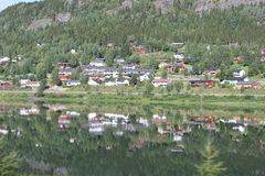Mirror view of mountain, cottages on lake water during travel Stock Images