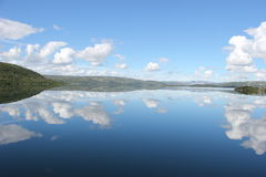 Mirror view of sky, clouds and mountain on lake water. A spectacular landscape of the mirror image in the lake on a sunny afternoon travelling in train in Norway Royalty Free Stock Photos