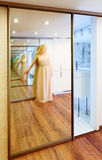 Mirror wardrobe in modern hall interior with infinity reflection. S and blurred person Stock Photos