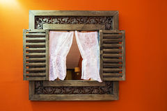Mirror in a wooden carved frame on an orange wall Royalty Free Stock Images