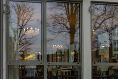 Mirrored cafe window facade with lustre at evening. In historical city of south germany royalty free stock photography