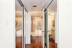 Mirrored closets and bathroom. Interior hallway with walk through mirrored closets to bathroom stock images