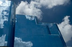Mirrored glass office building. A mirrored office building with a blue sky with clouds background stock photography