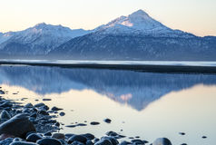 Mirrored Mountains. Blue tinted mountain is reflected in still water Stock Image