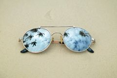 Mirrored sunglasses close up on the beach sand with palm trees reflection.  Royalty Free Stock Image