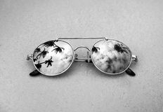 Mirrored sunglasses close up on the beach sand with palm trees reflection in black and white.  Stock Photos