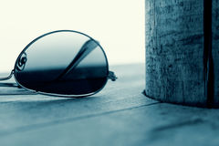 Mirrored Sunglasses Detail on the Wooden Background. Fashion Concept in Cyan. Mirrored Sunglasses Detail on the Wooden Background Close Up and Selective Focus Royalty Free Stock Image