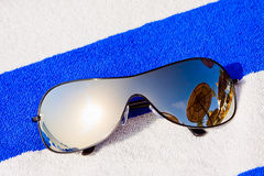 Mirrored sunglasses reflecting sun and sunshade Stock Images