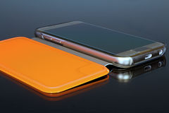 Mirroring the gold mobile phone in orange case. Mobile phone in case. Mirroring the gold mobile phone in orange case Stock Photo