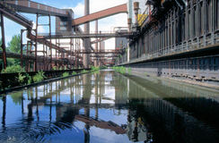 Mirroring an industrial plant. Look onto a water basin, built to take glooming coke and mirroring the coke plant on the industrial monument Kokerei Zollverein at Stock Photography