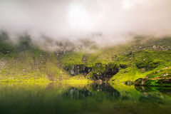 Mirroring lake on the mountain fog.Useful as background. Stock Images