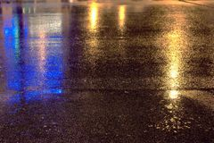 Mirroring lights on night rain road asphalt royalty free stock images