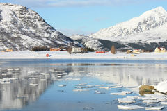 Mirroring in Lofoten's fjord. The small village of Skreda mirroring in the fjord stock image