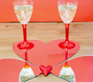 Mirroring of two champagne glasses and little heart Royalty Free Stock Images