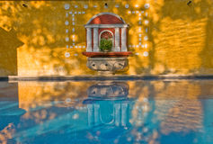 Mirroring wall-fountain. Wall fountain, decorated with white shells, mirroring in the blue water basin, seen in a romantic hotel-court in antigua, guatemala Royalty Free Stock Photo