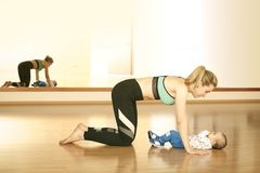 Mirroring young mother enjoying exercice in fitness studio with her baby boy. Young fitness women exercising with her infant son Stock Photos