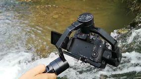 Mirrorless camera with electronical gimbal shooting waterfall in slow motion.