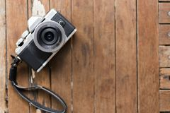 Mirrorless camera white and black color on a old wooden Board Royalty Free Stock Photo