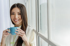 Mirthful asian woman drinking hot beverage Royalty Free Stock Photos