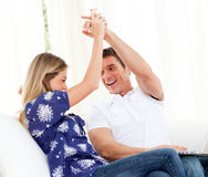 Mirthful couple using a laptop sitting on sofa Stock Photos