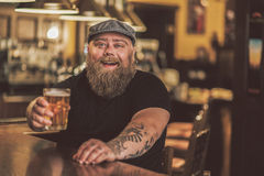 Mirthful fat guy spending evening in pub Royalty Free Stock Image
