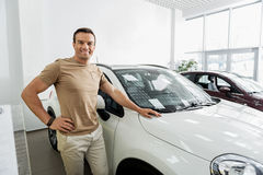 Mirthful man situating near new car Royalty Free Stock Photo