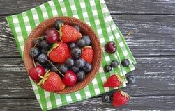 Mirtilli, antiossidante organico dell'asciugamano di freschezza della ciliegia delle fragole su una vecchia estate di legno nera immagine stock