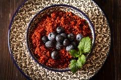 Mirtilli e lamponi della quinoa su un piatto con il backgro nero Immagini Stock