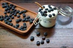Mirtilli freschi con yogurt in vetro sulle tavole di legno fotografia stock