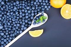 Mirtilli freschi e maturi in un cucchiaio di legno Un mucchio delle bacche organiche e dell'agrume succoso su un fondo blu scuro Fotografie Stock Libere da Diritti